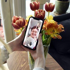 Kuvassa lapsi ja vanhus juttelevat videoyhteyden avulla.