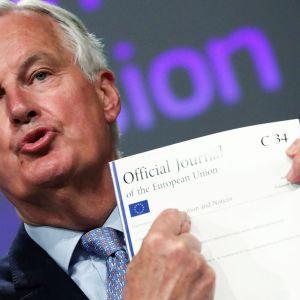 Kuvassa Michel Barnier esittelee dokumentteja tiedotustilaisuudessa.