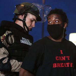 Kuvassa poliisi pidättää afroamerikkalaisen miehen.