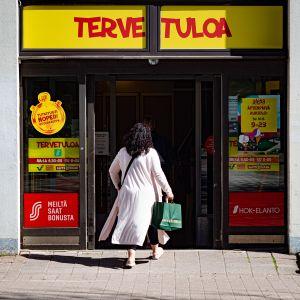 Nainen menossa sisään ruokakauppaan.