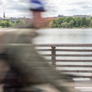 Pyöräilijä ajaa kesällä polkupyörällä sillalla Helsingissä.