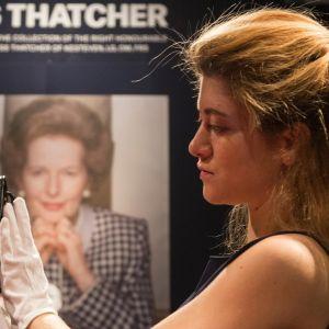 Huutokauppakamarin työntekijä pitelee hansikoiduin käsin pientä mustaa käsilaukkua. Taustalla juliste, jossa Thatcherin kuva ja nimi.