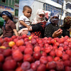 Kuvassa uiguurinaisia hedelmätorilla Urumqin kaupungissa Xinjiangin maakunnassa Kiinassa.