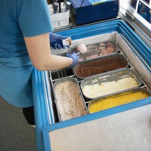 Jäätelönmyyjä pyörittelee jäätelöpalloa.