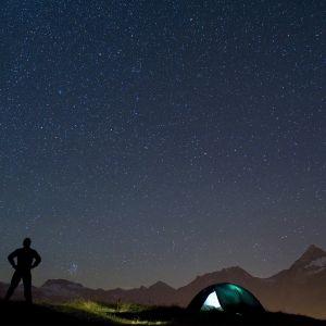 Kuvassa on telttailija ja tähtitaivas