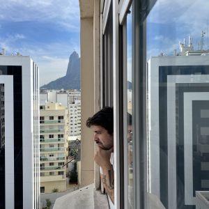 Alvaro Seixas, taideprofessori, taiteilija, Rio de Janeiro, Brasilia. Alvaro Seixas katsoo ulos asuntonsa ikkunasta Botafogon kaupunginosassa Rio de Janeirossa, jossa hän on koronakaranteenissa. Kuva otettu kesäkuussa 2020.