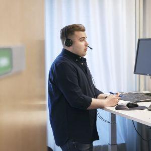 kriisityöntekijä päivystämässä työpöydän ääressä MIELI Suomen Mielenterveys ry:n kriisipuhelimessa.
