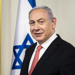 Pääministeri Benjamin Netanjahu katsoo kameraan seisten Israelin lipun edessä.