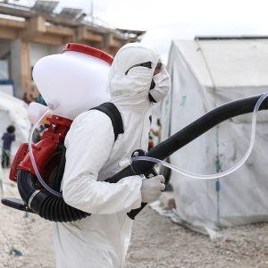 """Vapaaehtoisen järjestön """"'Violet Organization"""" - jäsen suojavarusteissa desinfioi telttakylää 9. huhtikuuta Idlibissä."""