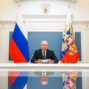 Putin pöydän ääressä. Hänen kuvansa heijastuu pöydän kiiltävältä pinnalta.