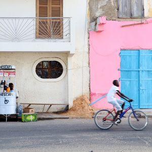 Kuvassa on siirtomaa-aikaisia taloja, hedelmäkioski ja pyöräilijä Saint-Louis'ssa, Senegalissa.