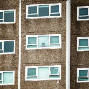 Nainen katsoo ulos eristetym kerrostalon ikkunasta Australian Melbournessa.