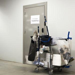 Laitossiivoojan siivousvälineet työntekijöiden taukotilan oven edustalla.