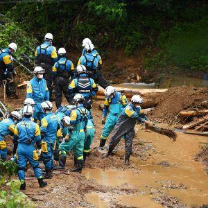 Japanilaiset pelastustyöntekijät etsivät maanvyöryssä kadoneita Tsunagissa.