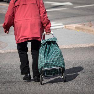 Vanhus vetää perässä vedettävää kauppakassia.