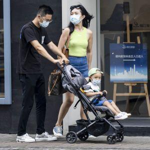 Pariskunta kadulla, mies työntää lastenkärryjä.