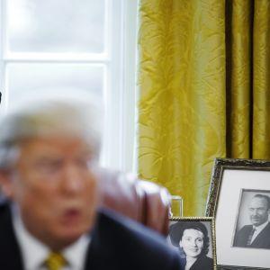 Kuvassa on Donald Trump toimistollaan.