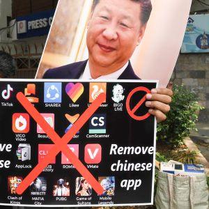 Mielenosoittaja pitää kiinalaisia sovelluksia vastustavaa kylttiä ja Kiinan presidentin kuvaa