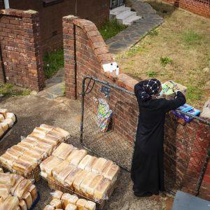 Kuvassa nainen valmistelee hyväntekeväisyysruokaa Etelä-Afrikassa toukokuun puolivälissä 2020.