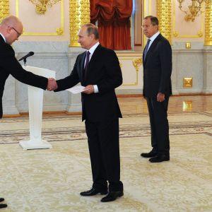 Suurlähettiläs Mikko Hautala kättelee presidentti Vladimir Putinin kanssa.