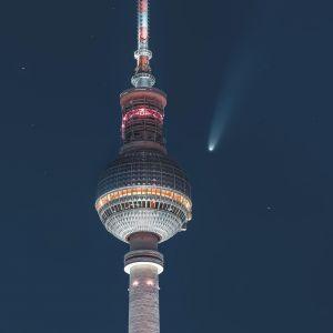 Berliinin tv-tornin huippu, taivaalla muutamia tähtiä ja pyrstöllinen komeetta.