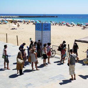 Kuvassa ihmiset jonottavat barcelonalaiselle uimarannalle.