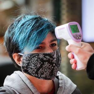 Ostoskeskuksen työntekijä mittaa ruumiin lämpötilas otsasta asiakkaalta ennenkuin hän saa mennä sisään ostoskeskukseen.