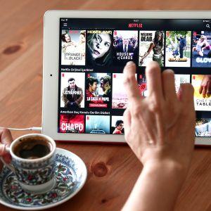 Nainen selaa padilta Netflixin tarjontaa kahvilassa Istanbulissa.