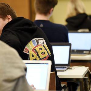 Yo-kokelaita ja kannettavia tietokoneita juuri ennen ylioppilaskirjoituksien äidinkielen lukutaidon kokeen alkua.