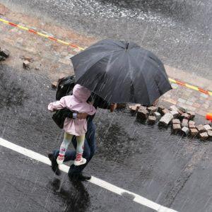 Mies kantaa lasta sateenvarjon alla rankkasateessa Helsingissä.
