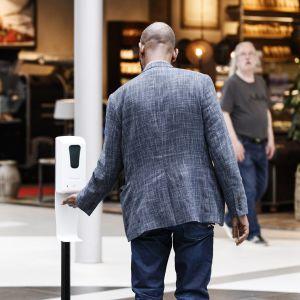 Mies käyttää käsidesiä kauppakeskus Itiksessä Helsingissä 20. heinäkuuta