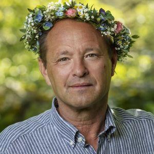 Professori Björn Olsen kukkaseppele päässään. Kaikki Ruotsin radion kesäpuhujat saavat seppeleen päähänsä.