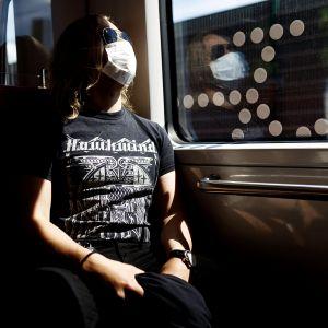 Kasvomaskia käyttävä matkustaja metrossa Helsingissä .