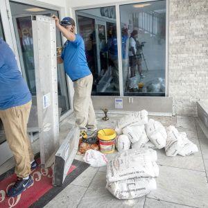 Työntekijät suojaavat apteekin sisäänkäyntiä paneeleilla ja hiekkasäkeillä.