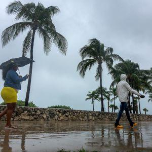 Ihmisiä kävelee sateisella kadulla