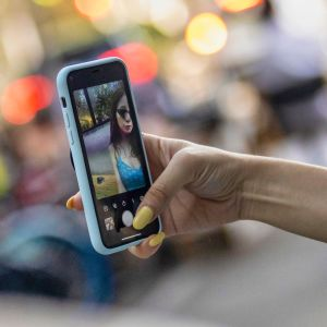 Nainen kuvasi itseään puhelimella Shanghaissa elokuun alussa. Kiinalaissovellus Tiktok on noussut maailmanpolitiikan kuumaksi perunaksi.