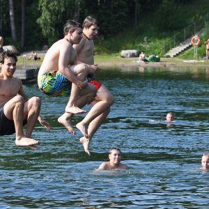 Pojat hyppäävät laiturilta veteen.