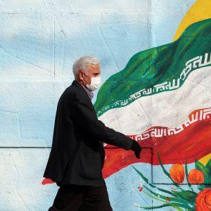 Mies kävelee Iranin lippua esittävän muraalin ohi.