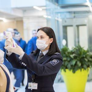 Virkailija mittaa lentomatkustajan lämpöä Chisinaun lentoasemalla Moldovassa.