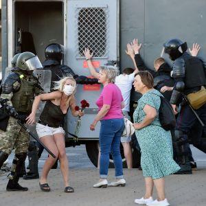 Mellakkapoliisiit pidättävät mielelnosoittajia Minskissä.