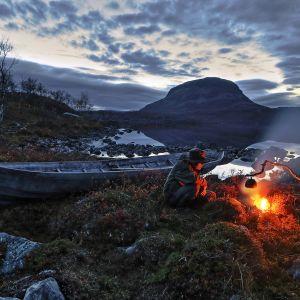 Kuvassa henkilö istuu nuotion äärellä illalla. Taustalla näkyy Saana-tunturi.