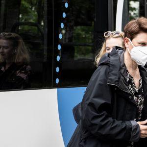 Nainen kasvomaskiin suojautuneena bussipysäkillä.