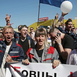 Suuri joukko työläisiä kulkee kadulla. Eturivissä olevat kantavat plakaattia, jossa on venäjänkielinen teksti isoilla kirjaimilla.
