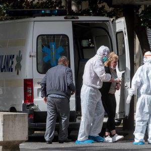 Koronaviruspotilasta siirretään ambulanssilta sairaalaan heinäkuussa Pohjois-Makedonian pääkaupungissa Skopjessa.