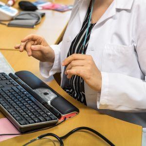 Lääkäri tietokoneen äärellä.