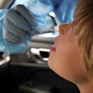 Lapsi koronatestissä HUSin lastensairaalan testauspisteellä sunnuntaina.