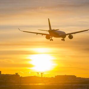 Finnairin Airbus lentokone laskeutuu Helsinki-Vantaan lentokentälle auringonlaskun aikaan talvi-iltana.