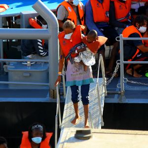 Siirtolainen ja hänen lapsensa rantautuu Maltalaisen laivan kannelta.