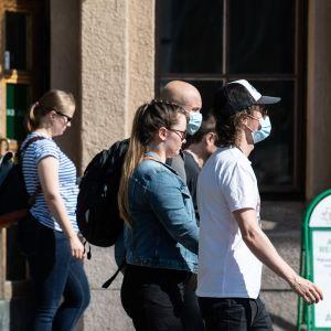 Ihmisiä kasvomaskit päällä Helsingin rautatieasemalla