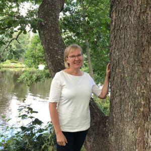 Nainen seisoo luontomaisemassa.